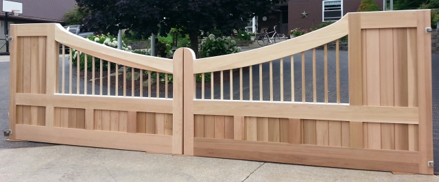 "Custom Concave wooden driveway gate with AZEK ""roof""."