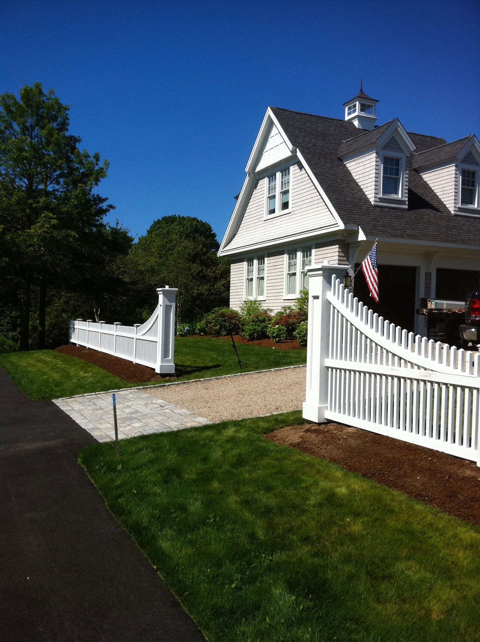 Pyramid picket fence with custom fence sweeps and genuine recessed panel columns